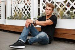 Modieuze knappe jonge mens in zwarte T-shirt met jeans stock afbeeldingen