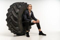 Modieuze knappe mens in zwarte kostuumzitting in band stock foto's