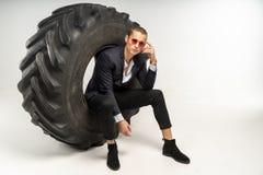 Modieuze knappe mens in zwarte kostuumzitting in band stock foto