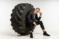 Modieuze knappe mens in zwarte kostuumzitting in band royalty-vrije stock foto's