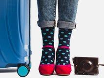 Modieuze koffer, de benen van vrouwen en heldere sokken stock fotografie