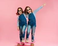 Modieuze leuke meisjes met skateboard stock foto