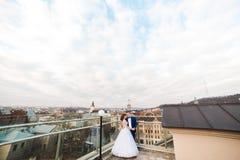 Modieuze luxebruid en elegante bruidegom die met tederheid op achtergrond van de oude stad Lviv koesteren royalty-vrije stock fotografie