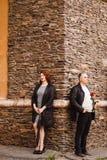 Modieuze man en vrouw die op middelbare leeftijd zich dichtbij de steenmuur bevinden van het huis in de zomer royalty-vrije stock foto