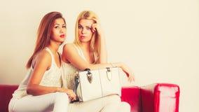 Modieuze meisjes met zakhandtas op rode laag Stock Foto's