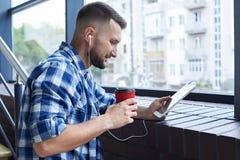 Modieuze mens het drinken koffie en het luisteren aan muziek Royalty-vrije Stock Foto