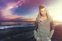 Modieuze mens met sweatshirt met een kap het overzees Kleurrijke zonsondergang Royalty-vrije Stock Foto