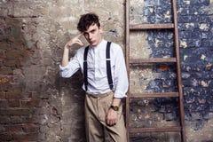 Modieuze mens in wit overhemd en beige broek, bretels die dichtbij oude houten ladder op bakstenen muurachtergrond stellen en bek stock fotografie