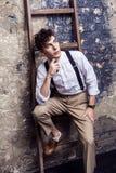 Modieuze mens in wit overhemd en beige broek met bretels die en op houten ladder op bakstenen muurachtergrond zitten stellen stock fotografie