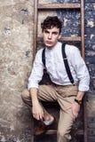 Modieuze mens in wit overhemd en beige broek met bretels die en op houten ladder op bakstenen muurachtergrond zitten stellen en royalty-vrije stock fotografie