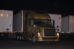 Modieuze moderne gouden semi vrachtwagen en aanhangwagens op nachtelijke parki royalty-vrije stock fotografie