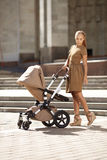 Modieuze moderne moeder op een stedelijke straat met een kinderwagen. Jong m Royalty-vrije Stock Afbeelding