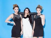 Modieuze mooie jonge meisjes die zich dichtbij een blauwe achtergrond verenigen Twee blonden en een brunette Het hebben van grapp Royalty-vrije Stock Afbeeldingen