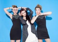 Modieuze mooie jonge meisjes die zich dichtbij een blauwe achtergrond verenigen Twee blonden en een brunette Het hebben van grapp Royalty-vrije Stock Foto