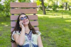 In modieuze mooie vrouw die het spreken op haar cellphone in het park roepen Mooie jonge vrouw die op cel spreekt royalty-vrije stock foto
