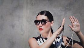 Modieuze mooie vrouw met zonnebril, parelhalsbanden en heldere geschilderde lippen stock afbeelding