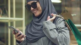 Modieuze Moslimvrouwen dragende aankopen, gelukkige het winkelen tijd, seizoengebonden kortingen stock video