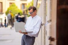 Modieuze oude mens die aan laptop werken die Internet in stad in openlucht in digitale nomadeoudste surfen die het moderne techno royalty-vrije stock afbeeldingen