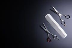 Modieuze Professionele Barber Scissors en witte kam op zwarte bac Stock Afbeeldingen