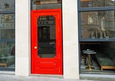 Modieuze rode deur in de stadskoffie stock fotografie
