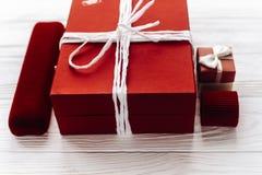 Modieuze rode huidig en en de dozen van luxejuwelen op witte roest Stock Foto