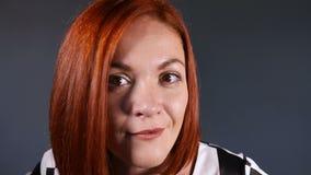 Modieuze roodharige vrouw die camera met nieuwsgierigheid bekijken stock videobeelden