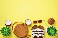 Modieuze rotanzak, succulente kokosnoot, birkenstocks, zonnebril op gele achtergrond banner Hoogste mening met exemplaarruimte stock fotografie