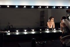 Modieuze schitterende bruid die make-up in saloo van de luxeschoonheid krijgen stock foto