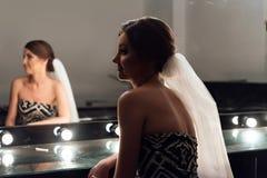 Modieuze schitterende bruid die make-up in saloo van de luxeschoonheid krijgen stock afbeeldingen