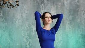 Modieuze sexy jonge meisjes modeltribunes in een lange blauwe kleding stock videobeelden