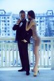 Modieuze sexy mens in kostuum met het sigar bekijken dame in korte dre Stock Fotografie