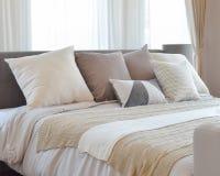 Modieuze slaapkamer binnenlands ontwerp met bruine gevormde hoofdkussens op bed en decoratieve schemerlamp Royalty-vrije Stock Foto