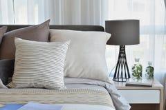 Modieuze slaapkamer met bruine gevormde hoofdkussens op bed Royalty-vrije Stock Foto