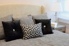 Modieuze slaapkamer met zwarte gevormde hoofdkussens op bed Stock Afbeelding