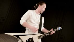 Modieuze solo gitarist met dreadlocks op zijn hoofd en in witte kleren op het zwarte expressively spelen als achtergrond stock footage