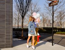 Modieuze stedelijke meisjes die in uitrusting met ballons dragen die op de Stadsstraat van New York lopen Stock Fotografie