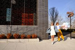 Modieuze stedelijke meisjes die in uitrusting met ballons dragen die op de Stadsstraat van New York lopen Royalty-vrije Stock Fotografie
