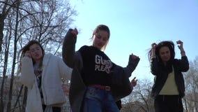 Modieuze tieners die en in het park dansen zingen stock videobeelden
