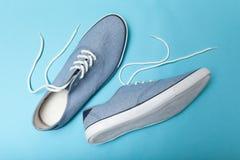 Modieuze toevallige blauwe tennisschoenen op blauwe achtergrond stock afbeeldingen