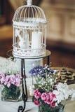 Modieuze verfraaide witte vogelkooi met blauwe en roze bloemen, stock fotografie