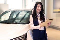 Modieuze verzekeringsagent die zich dichtbij de auto bevinden en een tablet houden royalty-vrije stock afbeelding