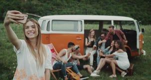 Modieuze vrienden die bier drinken en selfie bij de picknickpartij nemen in het midden van aard, die zich erachter van retro bevi stock video