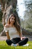 Modieuze vrolijke donkerbruine zitting onder een boom in een park stock foto