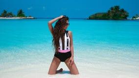 Modieuze Vrouw in bikini het suntanning op tropisch strand Vrij het slanke meisje stellen op exotisch eiland door mooie turkooise stock afbeeldingen