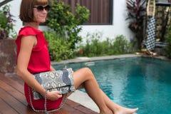 Modieuze vrouw in de rode zak van de het leer snakeskin python van de kledingsholding Elegante uitrusting Sluit omhoog van beurs  Royalty-vrije Stock Afbeelding