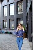 Modieuze vrouw die door smartphone in stad spreken, die jeans dragen Stock Afbeeldingen