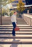 Modieuze vrouw die een vlucht van stedelijke treden beklimmen Stock Foto's