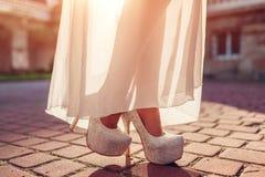 Modieuze vrouw die hoog gehielde schoenen en witte kleding in openlucht dragen Schoonheidsmanier stock fotografie