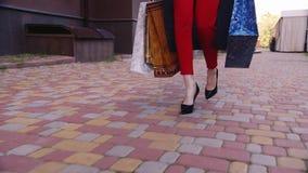 Modieuze vrouw die met het winkelen zakken op de stoep lopen In het beeld kan slechts de benen worden gezien stock videobeelden