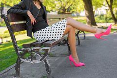 Modieuze vrouw die met roze schoenen op bank in park zitten royalty-vrije stock afbeelding